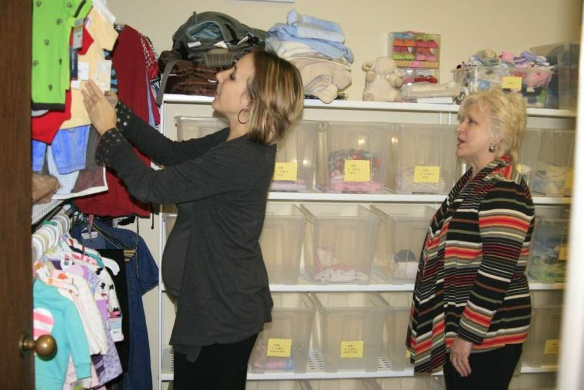 Erin Stubbs peruses the racks of baby clothes with Executive Director Charlotte Earhart at the Alpha Pregnancy Center located in Humble.