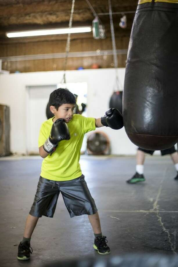 Marc Solis, 7, punches a heavy bag during a training session Jan. 16, 2014, at the Texas Hard-Hitters Boxing Club in Porter. Solis is not allowed to compete until he is 8 years old but has been training at the club for almost 14 months. Photo: ANDREW BUCKLEY