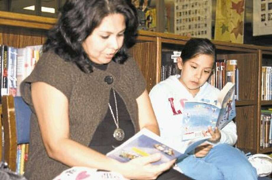 Maria Lara, left, with her daughter, Vanessa Lara, spend time reading several of the books featured at a past Humble ISD Children's Book Festival. / @WireImgId=2657910