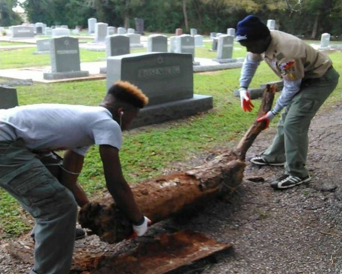 Baker receives assistance from fellow Scout, Marlon, in removing a tree trunk from the cemetery.