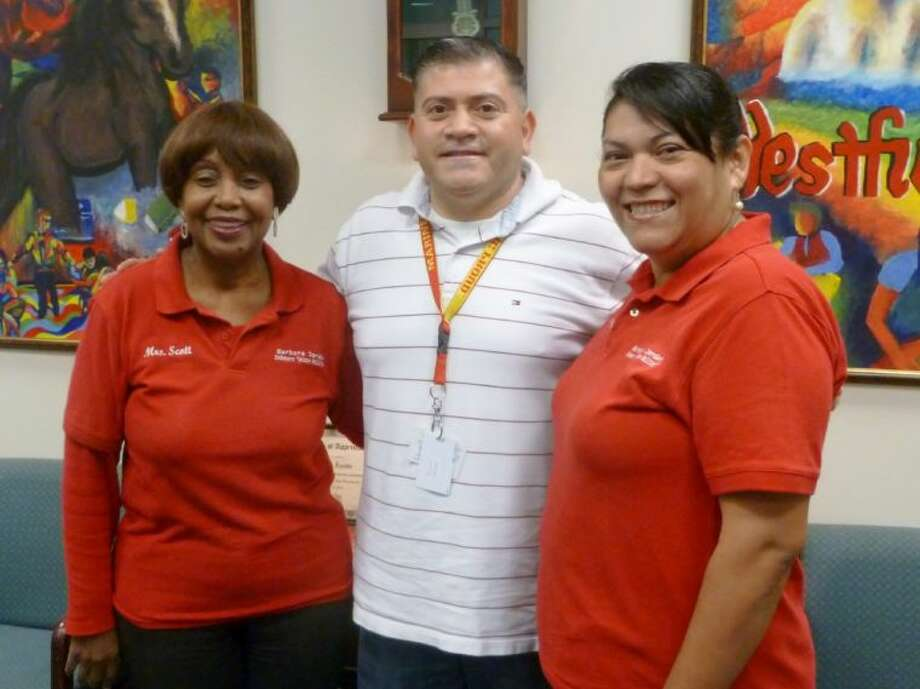 Thelma Scott and volunteer Evelyn Gonzales meets with special education teacher Daniel Stoltz to spread her program.