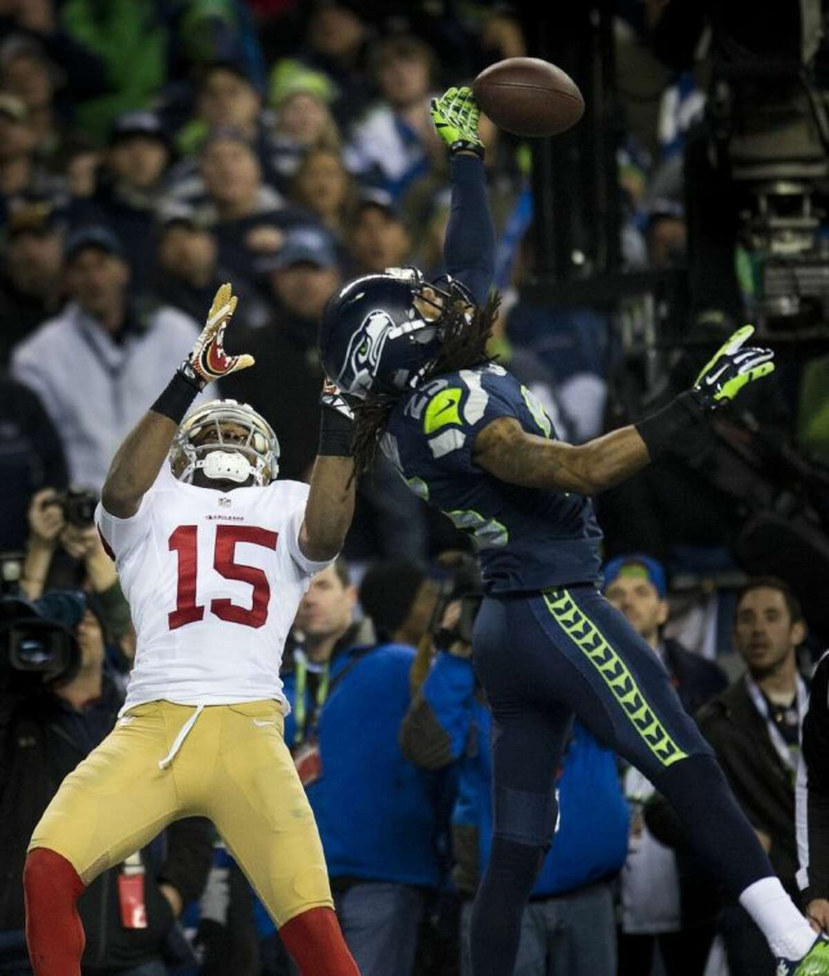 Seahawks cornerback Richard Sherman, right, bats the ball to teammate Malcolm Smith for the interception that sealed his team's Super Bowl berth on Sunday night.