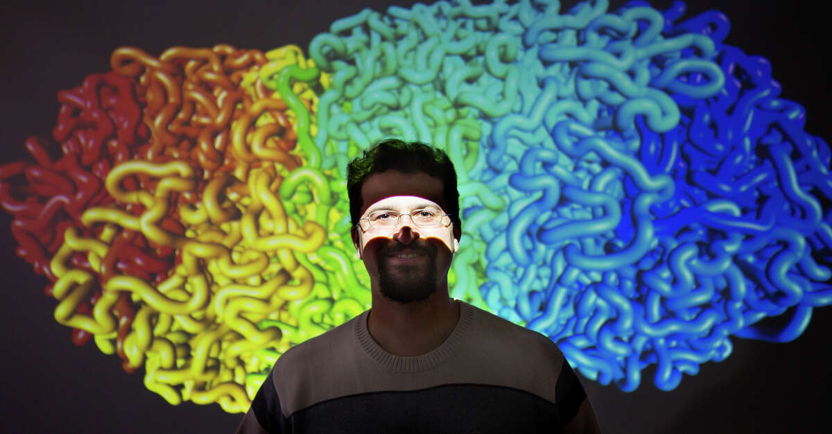 Dr. Erez Aiden stands in front of a projected image of a tension globule, a model of how the genome folds inside the cell, at Baylor College of Medicine, Oct. 19, 2015, in Houston. Research at Baylor continues to build off the initial cracking of the human genome.