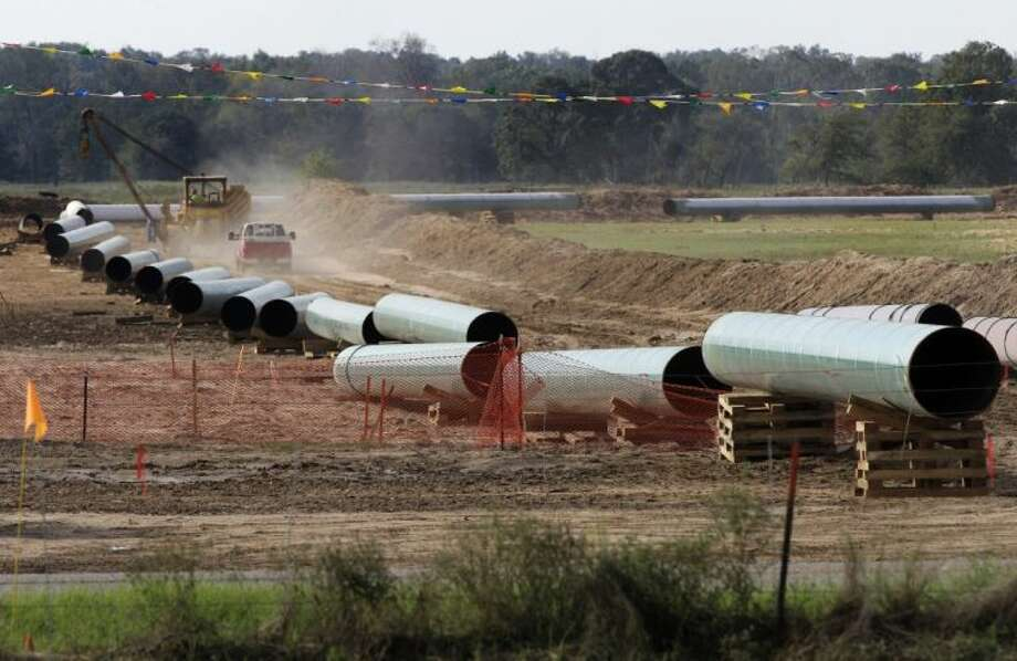 In th is Oct. 4, 2012 file photo, large sections of pipe are shown on a neighboring property to Julia Trigg Crawford family farm, in Sumner, Texas. On Wednesday, TransCanada said in a statement on its website that it is delivering oil through the Gulf Coast portion of its proposed Keystone XL pipeline, from a hub in Cushing, Okla., to Houston-area refineries.
