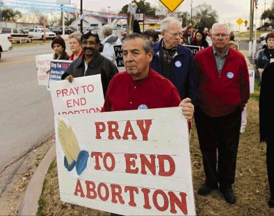 Tony Velasquez helps lead anti-abortion protesters on a walk from Sacred Heart Catholic Church to the intersection of Davis St. and North Frazier St. in Conroe Wednesday. Church members protested the passing of Roe v. Wade, the Supreme Court ruling that struck down anti-abortion laws 41 years ago Wednesday.
