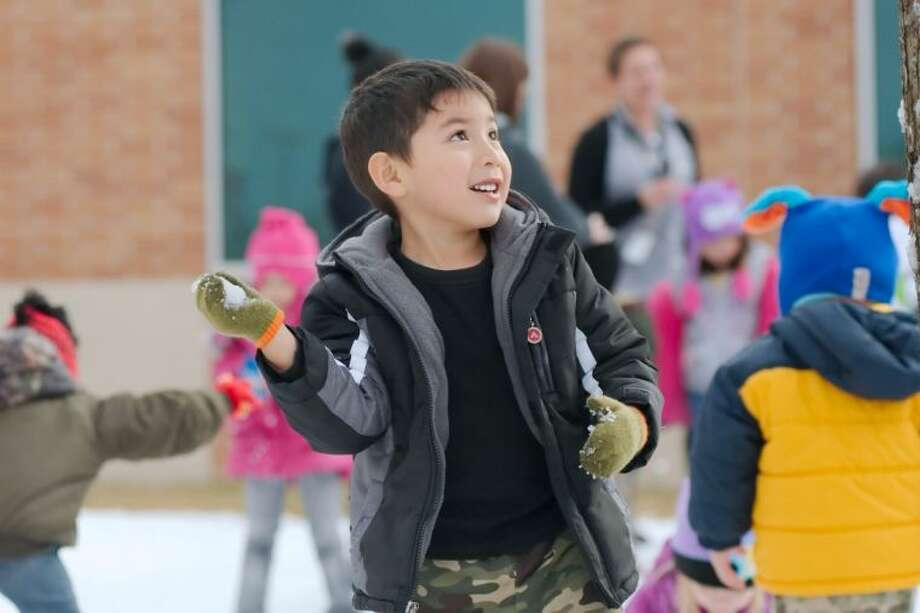 Jauquin Lopez builds a snowball and looks for a target during the Deer Park Early Childhood Center Snow Day Thursday, Jan. 23.