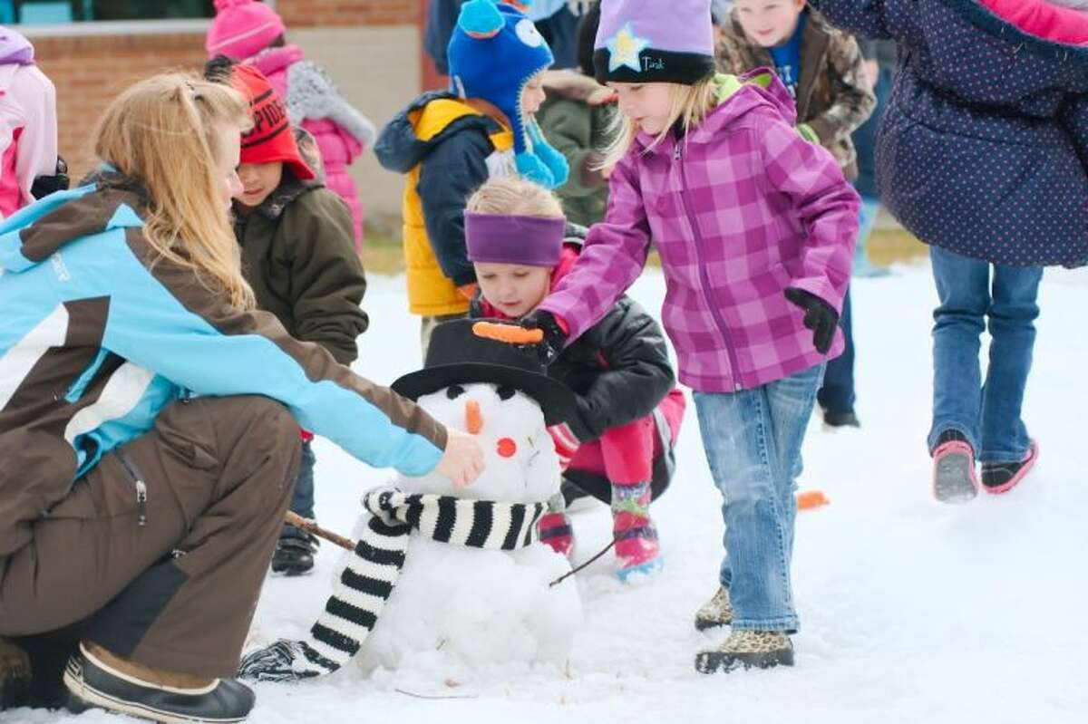 LeightonFruin and Chloe Petty work on a snowman during the Deer Park Early Childhood Center Snow Day Thursday, Jan. 23.