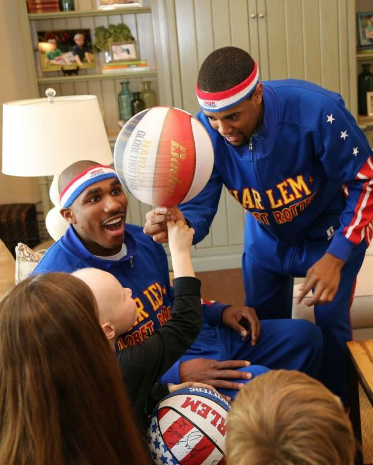George Gring gets help spinning a basketball on his finger from Globetrotter Cheese Chisholm (right), to the delight of Thunder Law.