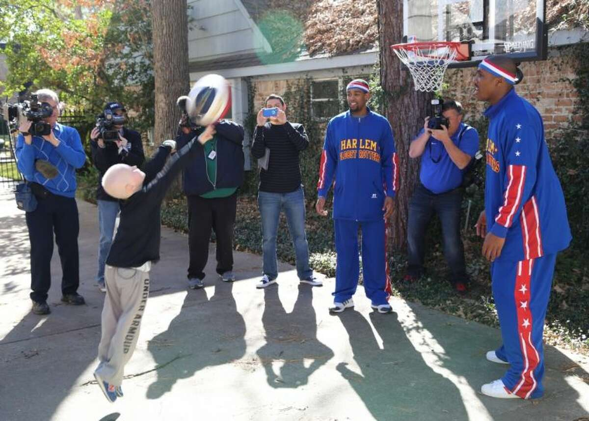 George Gring launches a shot on his family's Memorial-area home under the tutelage of Globetrotters Cheese Chisholm (left) and Thunder Law.