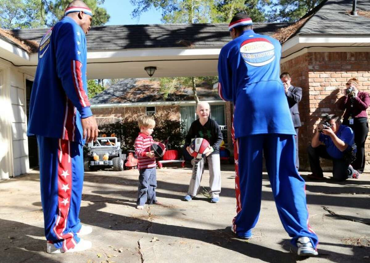 George Gring (center right) and his brother, Wade, learn ball handling from Globetrotters Thunder Law and Cheese Chisholm.
