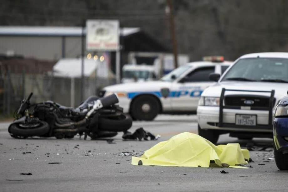 The body of an unidentified motorcyclist waits to be removed from the street after a police chase ended with a fatality. The driver of the motorcycle crashed into a blue Mustang GT and died at the intersection of Loop 494 and East Martin Drive in Porter Jan. 23, 2014. Photo: ANDREW BUCKLEY