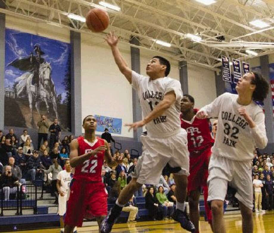 College Park's Keanu Andaya makes an acrobatic shot during a District 14-5A game against Oak Ridge on Friday night at College Park High School in The Woodlands. To view or purchase this photo and others like it, visit HCNpics.com. / The Conroe Courier/ The Woodland