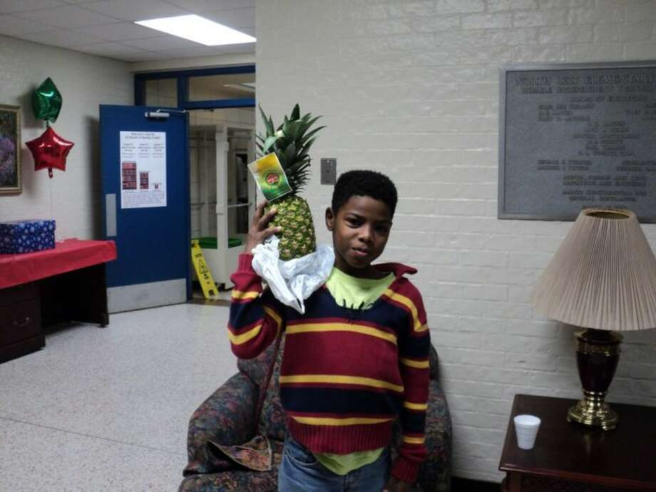 North Belt Elementary fifth grader Bray'veon Murray showing off a fresh pineapple.