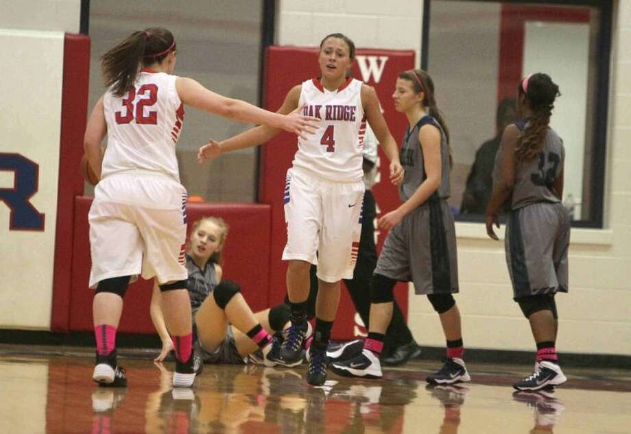 Oak Ridge's Jamy Smith (4) celebrates with Kelsey Scibek after drawing a foul during a District 14-5A game on Friday at Oak Ridge High School. To view or purchase this photo and others like it, visit HCNpics.com.