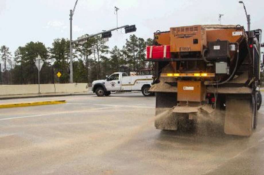 City of Conroe crews drop sand on a bridge near Wilson Road and Interstate 45 North in an effort to treat icy road conditions Tuesday morning. The mix of sleet and freezing rain ending by late morning, with partly cloudy skies clearing by late Tuesday night and colder temperatures dipping into the high to mid-20's overnight. Photo: Staff Photo By Ana Ramirez / Conroe Courier
