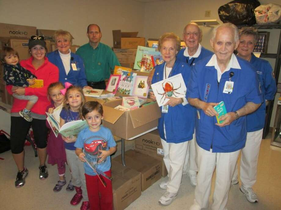 Enjoying their Barnes & Noble books from left, are Finn Rushing, held by mom, Sara Rushing; Elizabeth Parhem, and Harper and Graham Rushing. Also pictured, from left, are Volunteer Book Buster Chair Janie Dampier; Barnes & Noble Deerbrook Community Relations Manager Larry Williams; and Volunteer Readers Frances and Bob Herring, Dave Marshall and Harriett Denning.