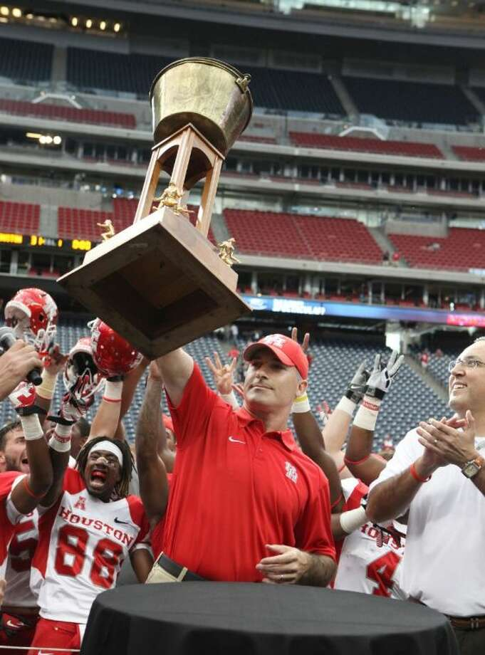 University of Houston Head Coach Tony Levine holds up the Bayou Bucket trophy after the Cougars defeated the Rice Owls 31-26 at Reliant Stadium in Houston on Saturday, September 21, 2013. Photo: Photo By Alan Warren