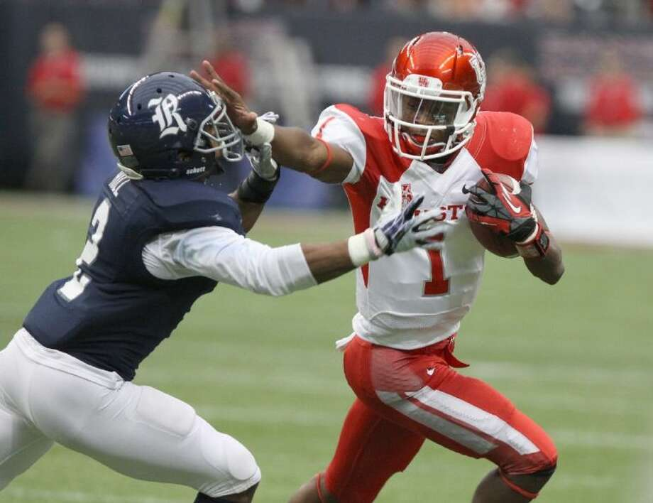 Houston's Greg Ward Jr. stiff arms Rice's Malcolm Hill during the 2013 Bayou Bucket at Reliant Stadium in Houston. Ward accounted for six touchdowns in a 59-14 victory against Texas State. Photo: HCN File Photo