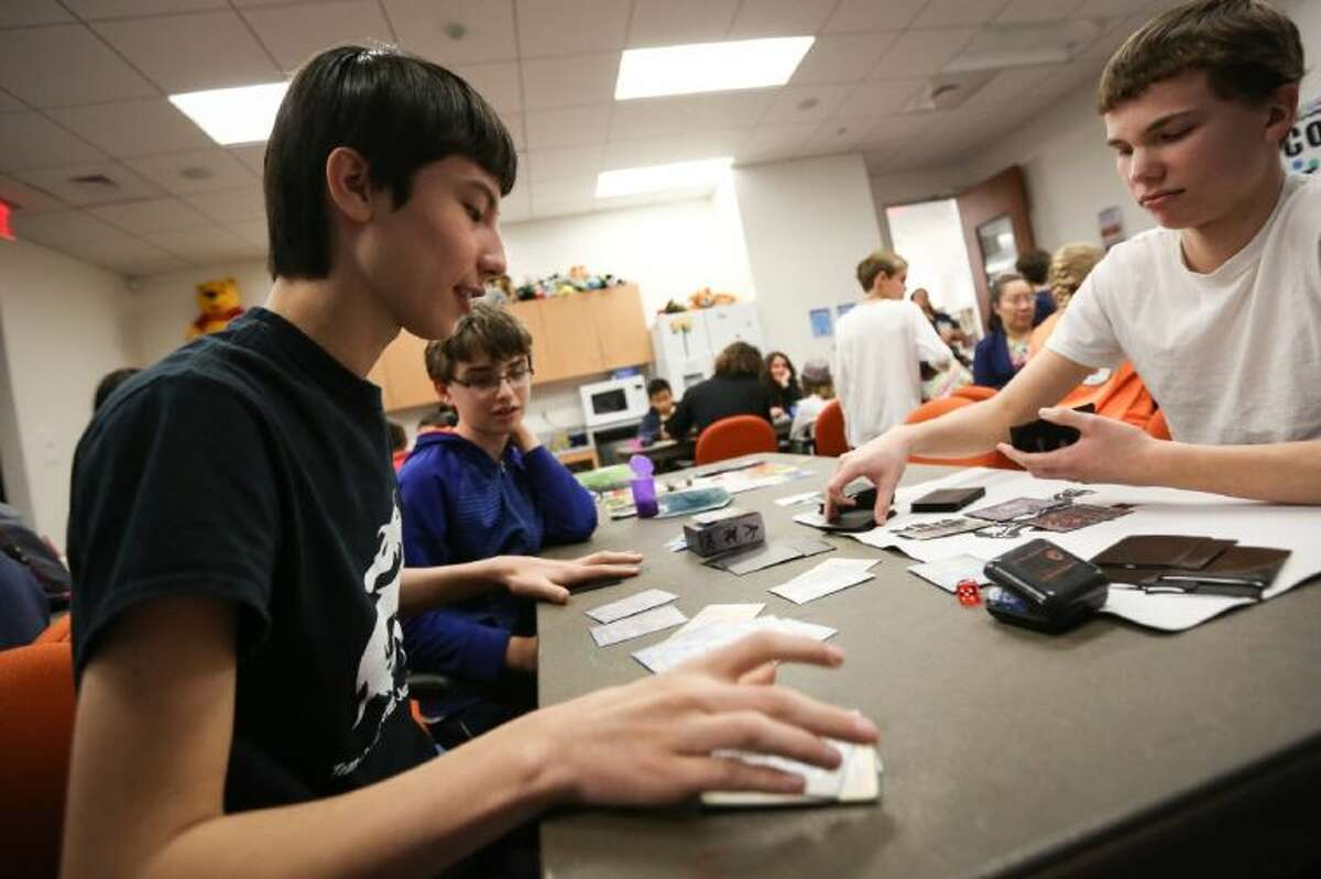 Connor McKee, the 2013 Texas Southwest Regional Pokemon Champion, left, plays a casual Pokemon match with Jose Flores, right, during a league meeting on Saturday, Feb. 15, in the LSC-Tomball library.