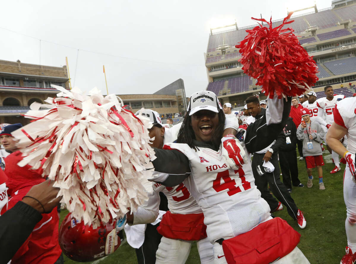 Houston linebacker Steven Taylor (41) celebrates while singing the school song and holding pom poms after they defeated Pittsburgh 35-34 in the Armed Forces Bowl NCAA college football game, Friday, Jan. 2, 2015, in Fort Worth, Texas. (AP Photo/Sharon Ellman)