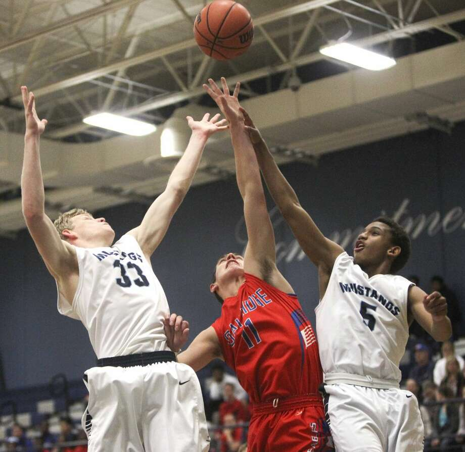 Oak Ridge's Trevor Graham tries to haul in a rebound against Kingwood's Matt Mallory and Brandon Burrell during a high school boys basketball game at Kingwood High School Friday. To view or purchase this photo and others like it, visit HCNpics.com. Photo: Jason Fochtman