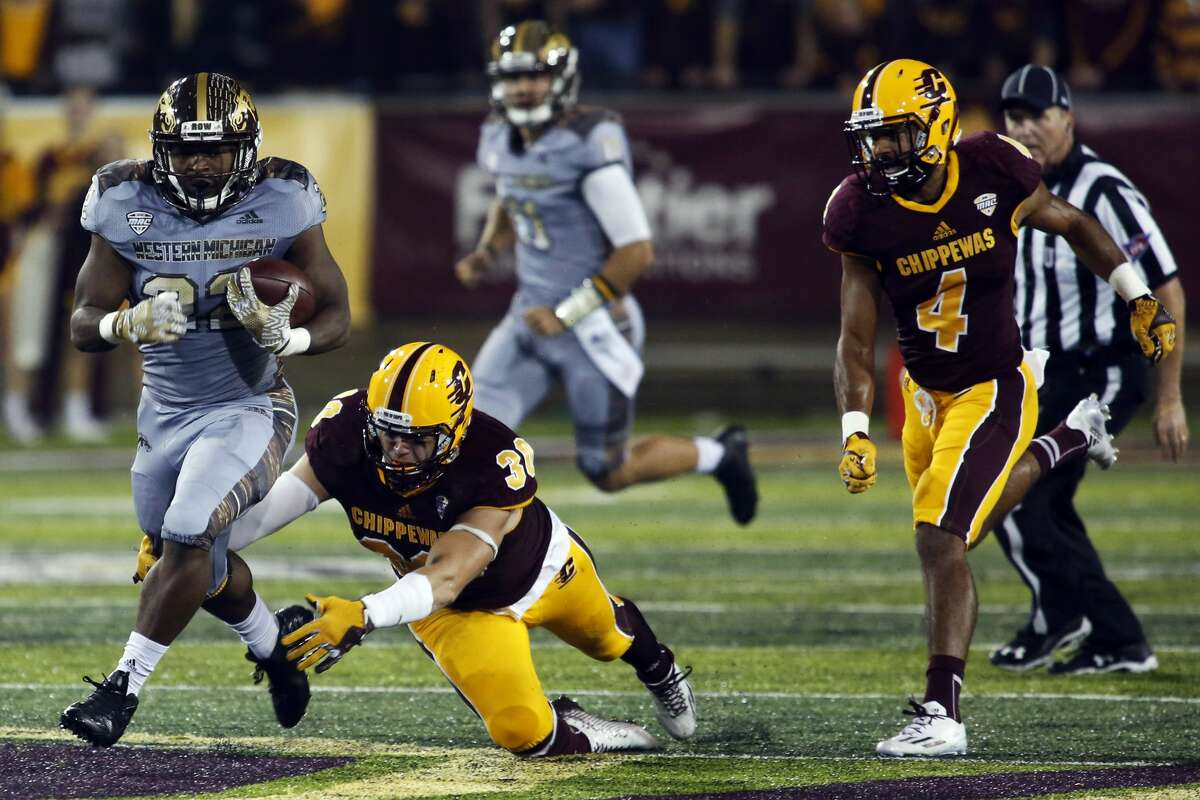 THEOPHIL SYSLO | For the Daily News Western Michigan University running back Davon Tucker run the ball before being tripped up by Central Michigan University defender Alex Briones in a game at the Kelly/Shorts Stadium in Mount Pleasant on Saturday.