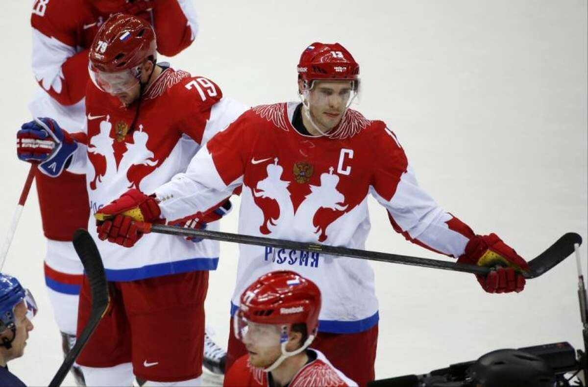 Russia defenseman Andrei Markov, left, and forward Pavel Datsyuk react after the Russians lost 3-1 to Finland in a quarterfinal game on Wednesday at the Winter Olympics in Sochi, Russia.