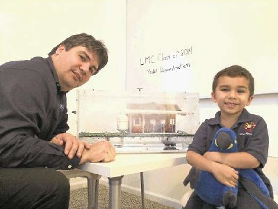 David Matos, with the Leadership Montgomery County Class of 2014, with his son Victor, show off the rainwater harvesting model the class is using as part of the educational tools to go with the class project of building rainwater harvesting systems at Bear Branch Sports Complex in The Woodlands, Oak Ridge Elementary and the North Montgomery County Community Center in Willis. / @WireImgId=2662851