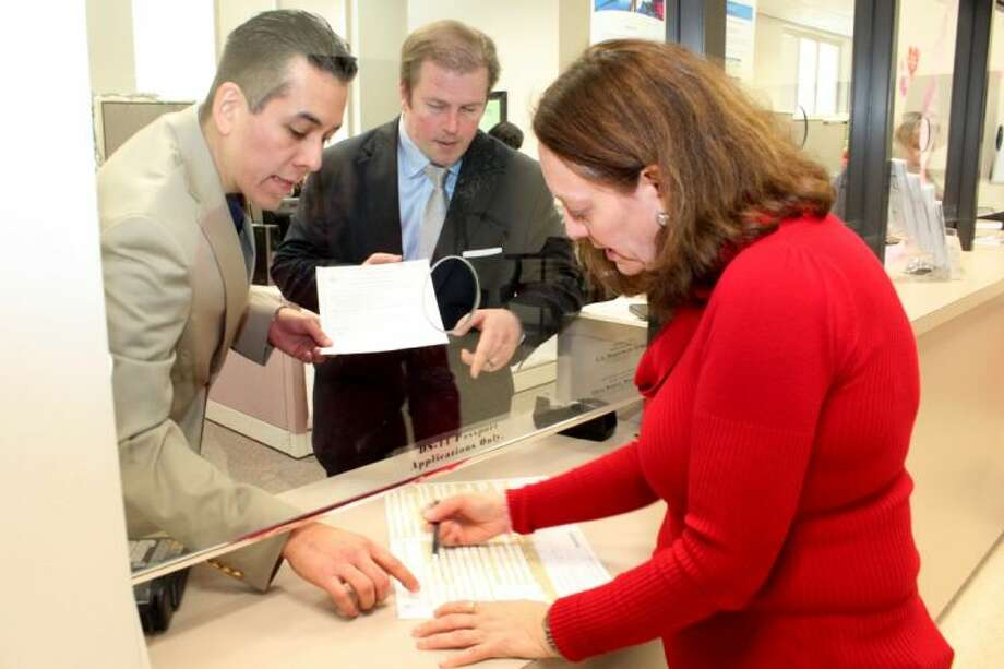 Luis G. Duque Jr, accounting manager at the District Clerk's Office, (left) and Harris County District Clerk Chris Daniel answer a question for a passport customer.