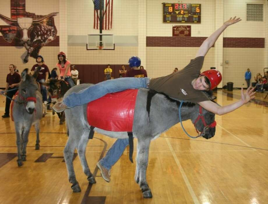 A Tarkington High School senior tries to stay aboard his donkey during the Feb. 21 donkey basketball game to raise funds for Project Graduation. Photo: STEPHANIE BUCKNER