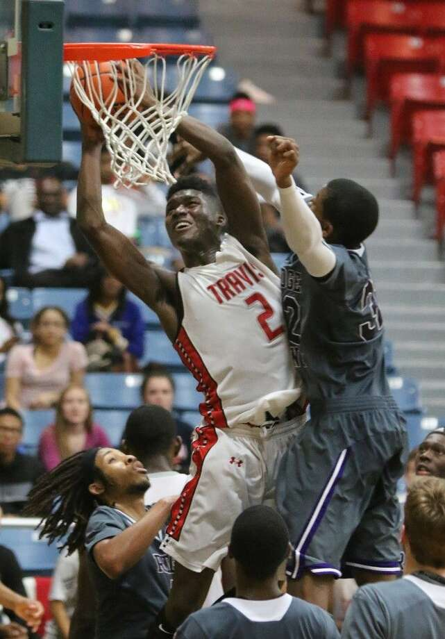 Travis' Juwan Williams goes up for a shot against Ridge Point's Amir Smith during their Dec. 12 game in the Fort Bend Raising Cane's Basketball Tournament at Wheeler Field House in Sugar Land. The Tigers lead District 23-6A with a 6-0 record. Photo: Alan Warren