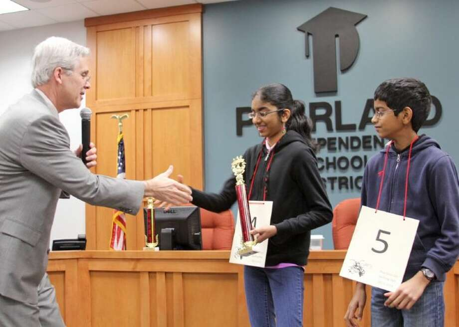 Superintendent Dr. John Kelly (left) awards a trophy to Pearland ISD Spelling Bee co-champions Shobha (middle) and Shourav Dasari. Photo: Courtesy Pearland ISD