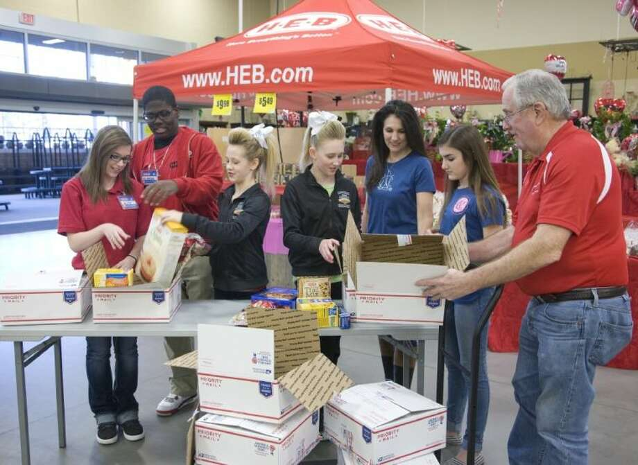 From left, H-E-B Partners Alix Van Handel and Elisha Finister III, local cheerleaders Alexa and Ellie, Tracy Bowling and daughter Brooke Bowling of the National Charity League and Dennis Bernhart of Cypress Cares. Photo: John Everett