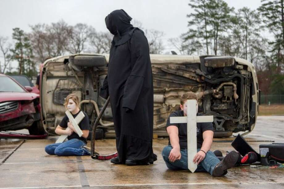 A Grim Reaper walks among students holding crosses during a re-enactment staged by Shattered Lives of Montgomery County at Willis High School earlier this month to show students the effects of poor decision-making. The Shattered Lives program will be presented to Magnolia students March 4-5. Photo: Ana Ramirez