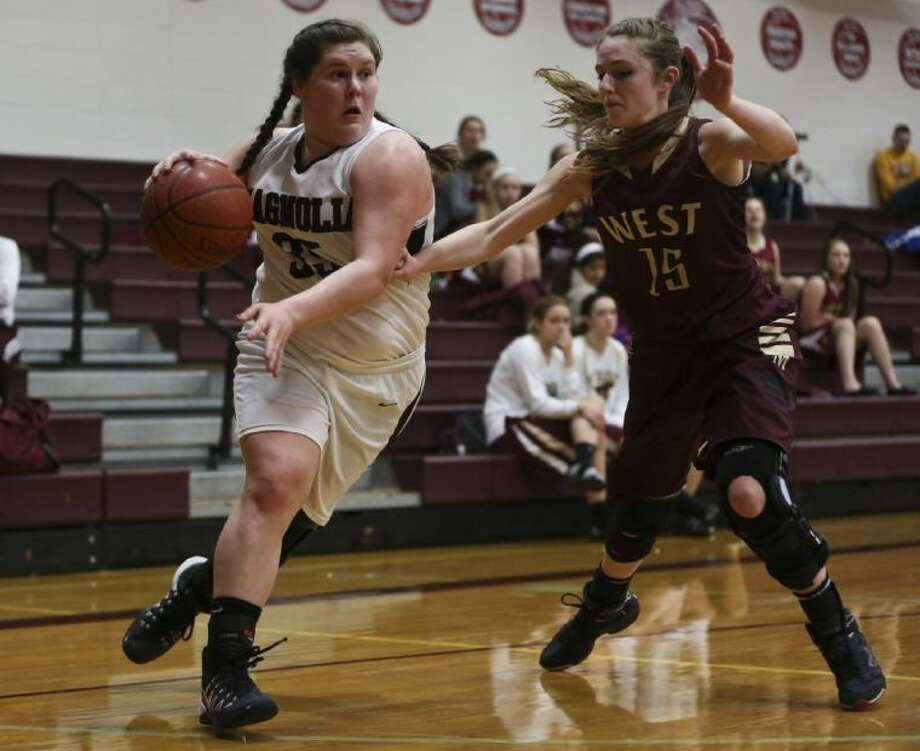 Magnolia's Jessica Bruti (35) drives for the basket while Magnolia West's Ashley Just (15) guards during the high school basketball game on Tuesday, Jan. 21, at Magnolia High School. To view or purchase this photo and others like it, go to HCNPics.com. Photo: Michael Minasi