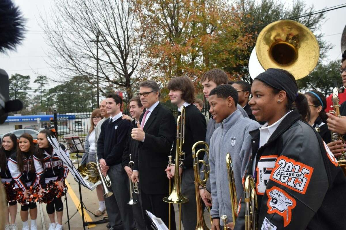 Governor Rick Perry joins the St. Pius X High School Band for photos before the opening ceremony at the Ibn Sina Foundation's Shepherd clinic on Jan. 12, 2015.