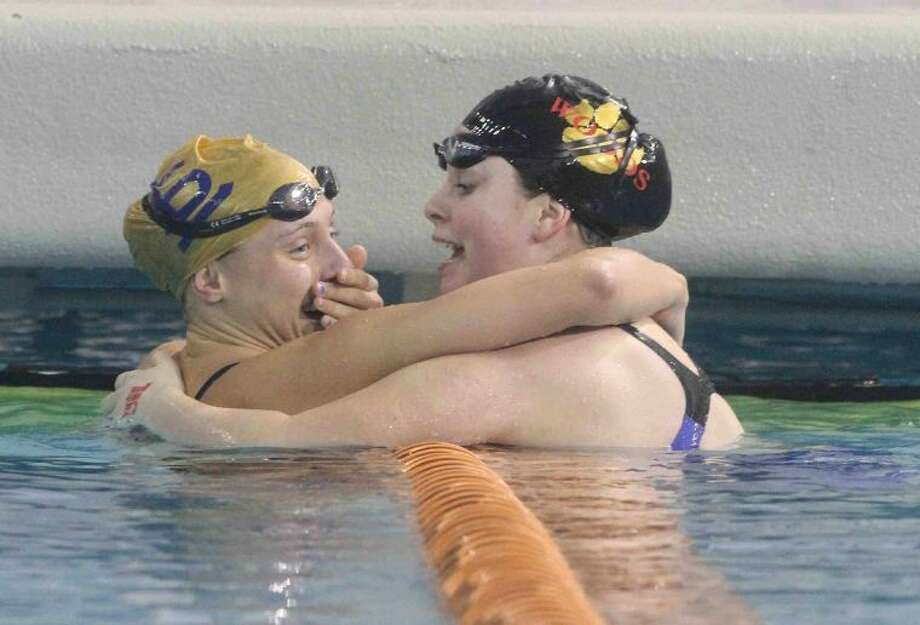 Seven Lakes' Lindsay Shabet, left, is congratulated by Cy Woods' Ashley Brem after the Class 5A girls 100-yard butterfly final Feb. 22 at the UIL Swimming and Diving State Championships in Austin. Visit HCNPics.com for more photos. Photo: Jason Fochtman