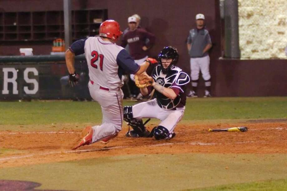 Pearland's Nathan Carter (16) applies the tag for an out as Dawson's Michael Becerra (21) slides into home plate last Thursday. Photo: KIRK SIDES