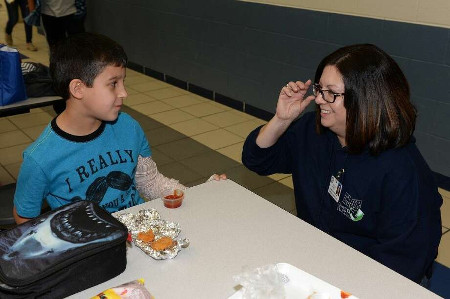 """Kristina Perez, director of community pgorams, speaks with Hemmenway Elementary School student Christopher Maldonado while serving in a teacher's stead on lunch duty as community programs' """"random acts of kindness"""" throughout the district in December. The community programs department was featured in Texas School Business' Eighth Annual Bragging Rights edition. Photo: Submitted Photo"""