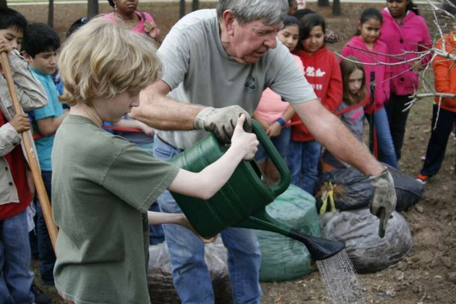 Keep Kingwood Green member and Oak Forest Elementary volunteer Hal Opperman helps fifth grader Connor Wilson water the newly planted tree.
