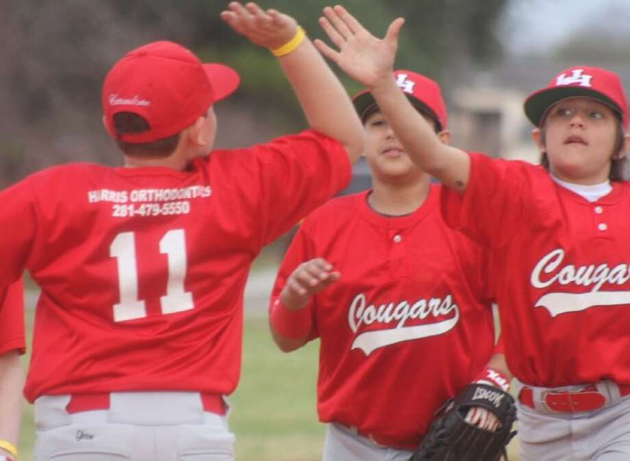 The Cougars trio of Cameron Cannline (11), Robert Salizar and Zach Menefee high-five one another after the defense turned in a 1-2-3 inning during their season opener with the Red Raiders Saturday afternoon. Photo: Robert Avery