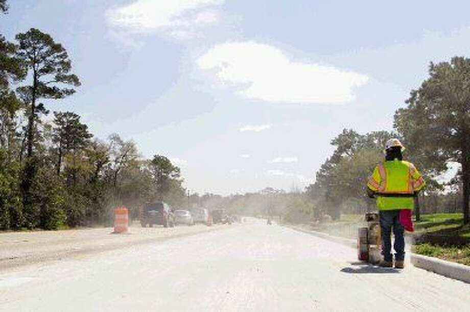 In this March 2014 file photo, construction crews work on widening a segment of Woodlands Parkway from East Panther Creek Drive to Grogan's Mill Road. Photo: Staff Photo By Ana Ramirez