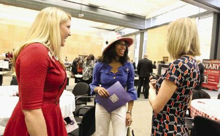 Tabitha Lenox, center, talks with Brooke Batchelor during the Whistle Stop Tour Luncheon put on by The Woodlands Area Chamber of Commerce at Lone Star College Corporate Center in The Woodlands Wednesday. Community members had the opportunity to visit with candidates.