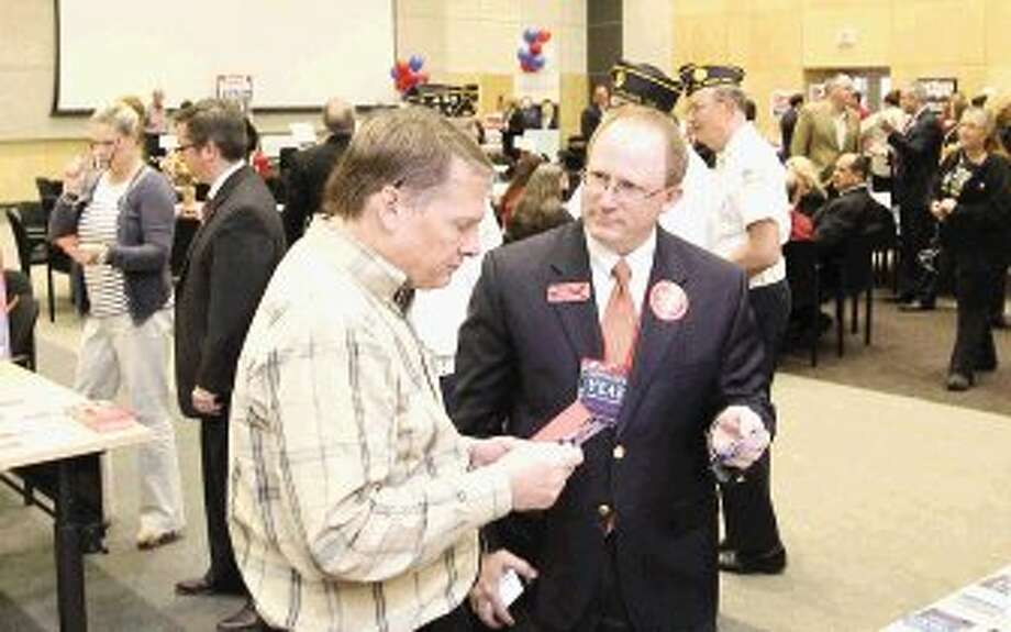 Kevin Patrick, right, candidate for judge for the Texas Court of Criminal Appeals, visits with a voters during the Whistle Stop Tour Luncheon put on by The Woodlands Area Chamber of Commerce at Lone Star College Corporate Center Wednesday. Community members had the opportunity to visit with candidates.
