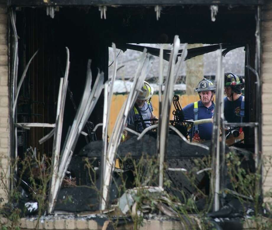 Firefighters take a closer look at the debris from the house fire on Forest Bend Avenue. Photo: Kar B Hlava