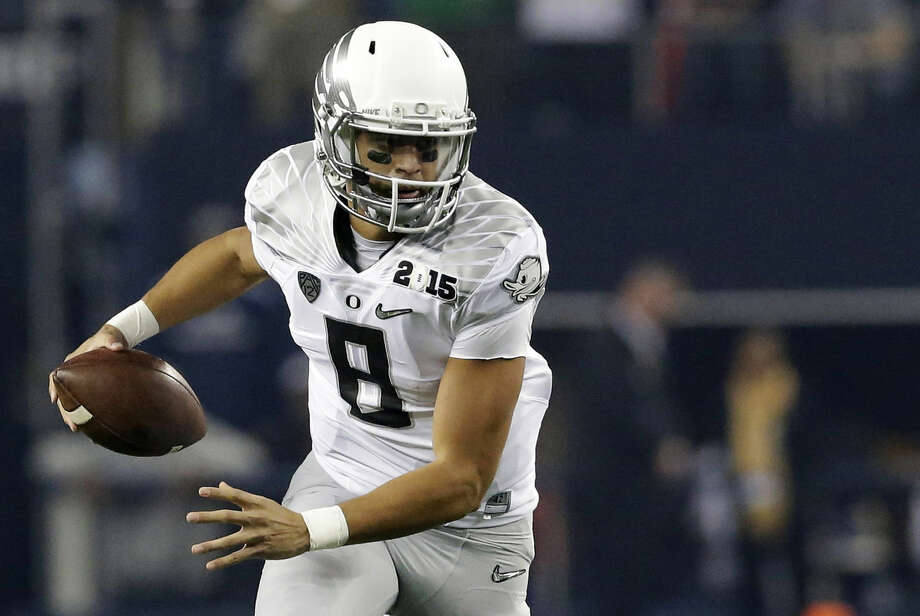 FILE - In this Monday Jan. 12, 2015, file photo, Oregon's Marcus Mariota (8) runs against Ohio State during the first half of the NCAA college football playoff championship game in Arlington, Texas. Mariota, the Heisman Trophy winner, has declared his eligibility for the NFL draft, in an announcement on Oregon's website, Wednesday, Jan. 14, 2015. (AP Photo/LM Otero, File) Photo: LM Otero