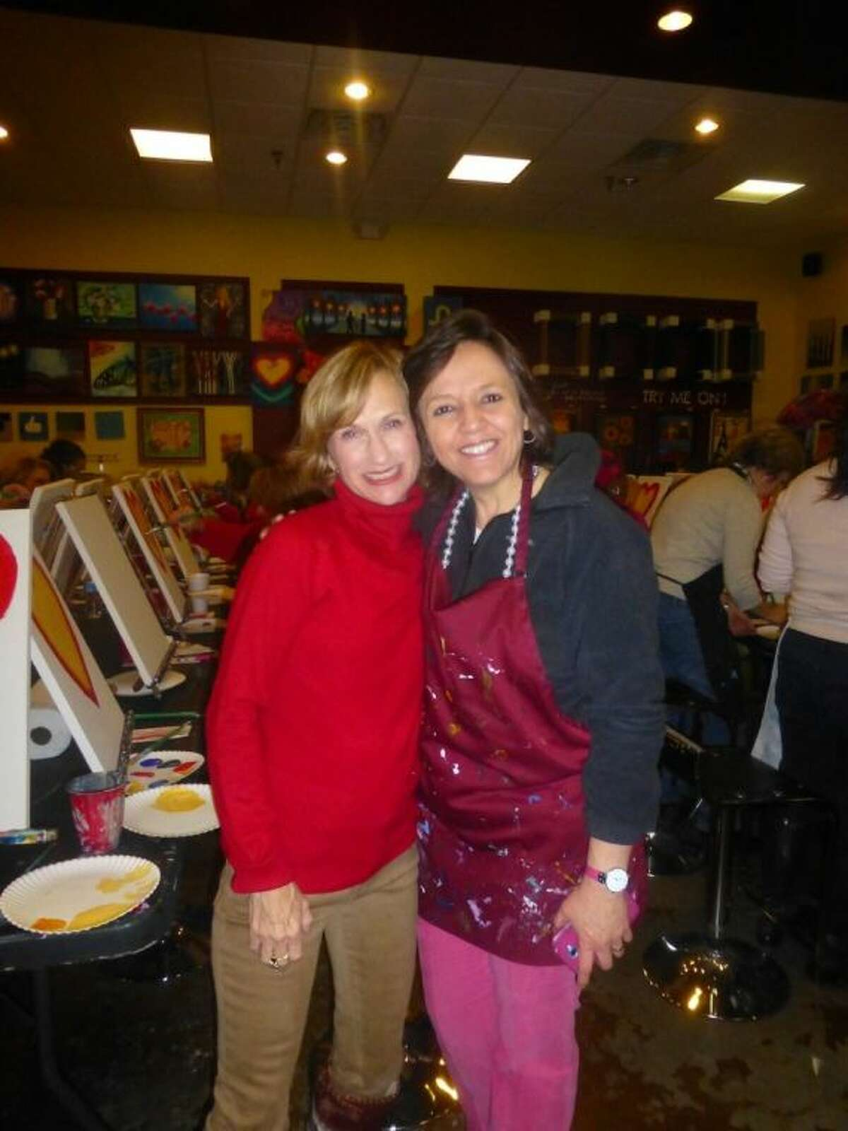 Laurie Hughes, (left) advanced practice nurse at the MD Anderson Regional Care Center in Sugar Land, welcomes friend and breast cancer survivor Myriam Saenz-Chavez to the February Breast Friends meeting held at Pinot's Palette in Sugar Land Town Square.
