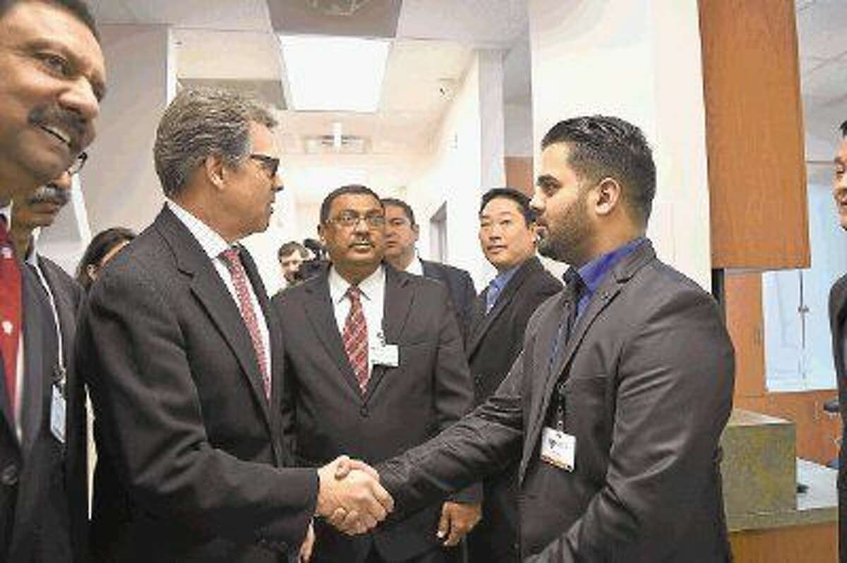 Governor Rick Perry shakes hands with dental office manager Rehan Khuwaja during a tour of the Ibn Sina Foundation clinic at 5021 North Shepherd Drive on Jan. 12, 2015. Ibn Sina Foundation CEO Aijaz Ali Khowaja (pictured center) gave the governor a tour of the facility before the opening ceremony.
