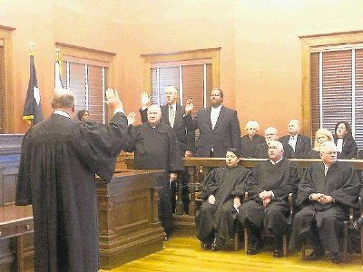 District Court Judge James Shoemake swear in (from bottom-left to upper-right) County Judge Bob Hebert, Precinct 2 Commissioner Grady Prestage and Precinct 4 Commissioner James Patterson.