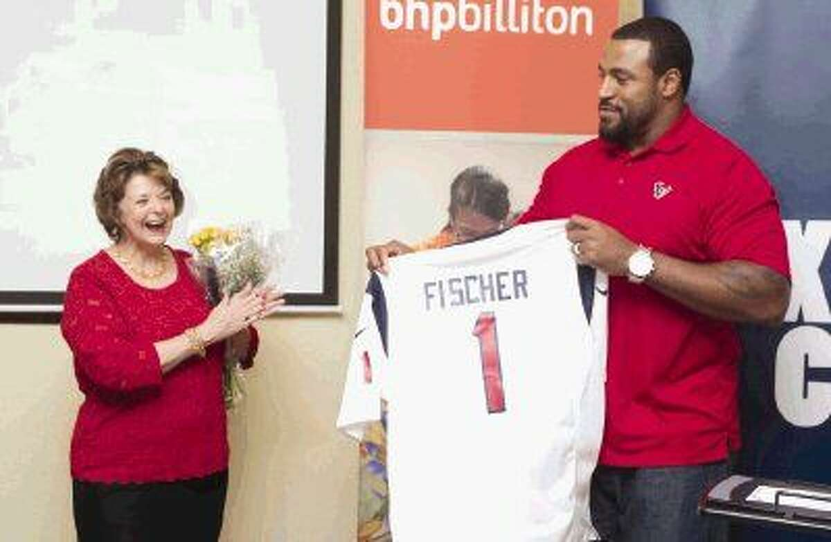 Marion Fischer laughs as Houston Texans offensive linemen Duane Brown presents a custom jersey during a ceremony Thursday at the Marion Fischer Community Center.